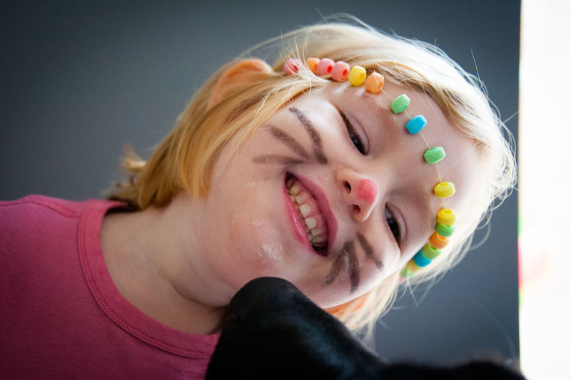 Close-up of smiling girl wearing candies with painted face