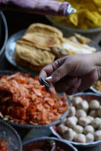 Cropped Hand Holding Coins Over Food In Containers At Market Stall
