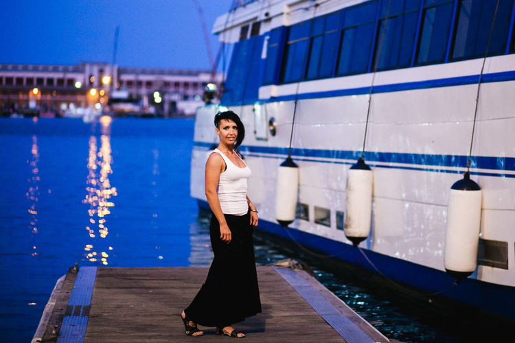 Full length portrait of young woman standing at harbor