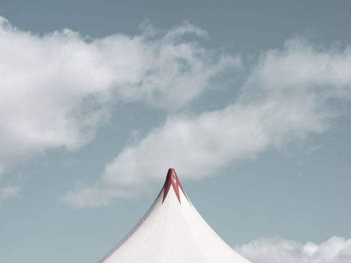 High section of tent against cloudy sky