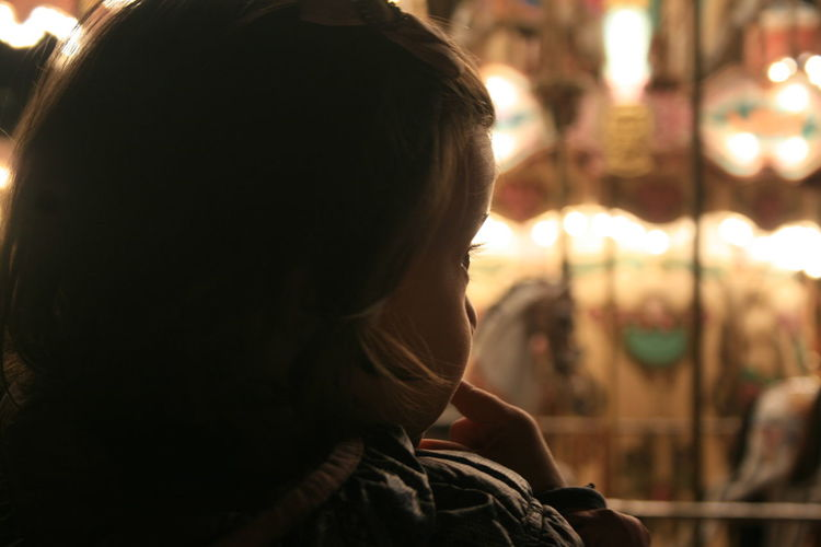 Rear view of baby girl looking away at illuminated amusement park during night