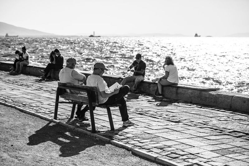People sitting by sea against sky during sunny day