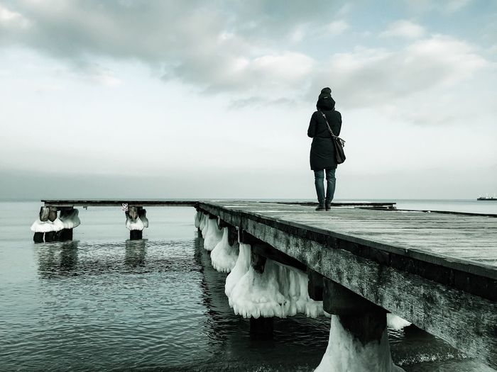Rear View Of Woman Standing On Jetty In Sea Against Sky