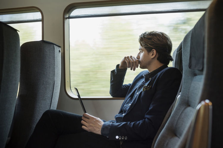 Full length of man using mobile phone while sitting in train
