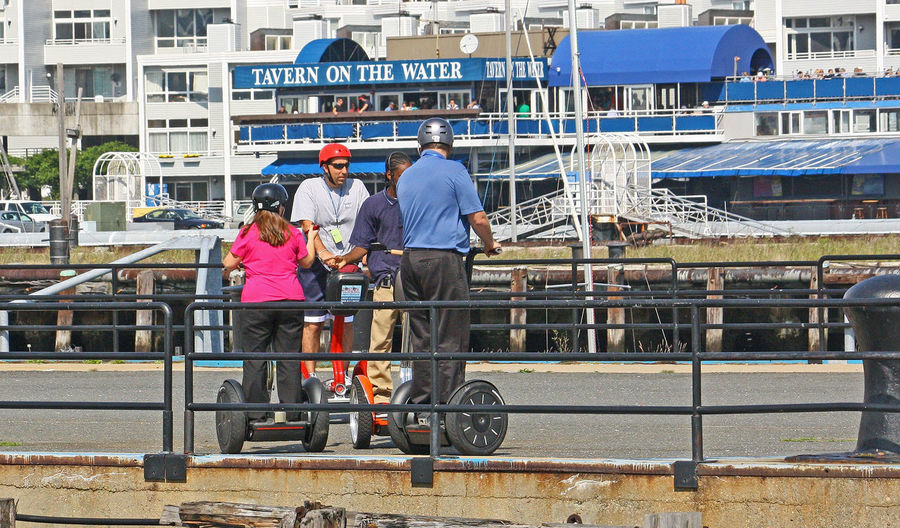 Boston Harbor Boston Massachusetts SegwayTours Adult Adults Only Architecture Building Exterior Built Structure Day Full Length Giroscope Helmets Helmets Required Leisure Activity Men Occupation Outdoors People Real People Rear View Segway Ride Segways In Boston Transportation Women