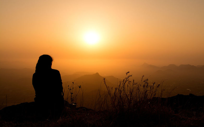 Life at Edge Adult Beauty In Nature Idyllic Leisure Activity Lifestyles Looking At View Mountain Nature Non-urban Scene One Person Orange Color Outdoors Real People Rear View Scenics - Nature Silhouette Sitting Sky Sun Sunset Tranquil Scene Tranquility