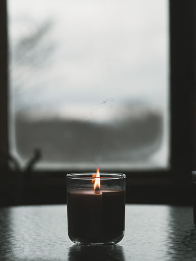 Close-up of lit candle against sky