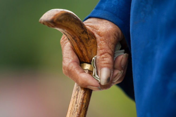 Cropped image of senior person holding walking cane