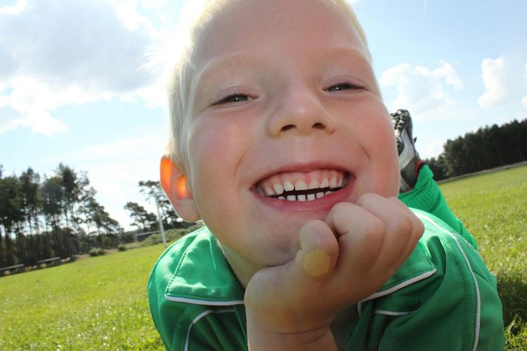 Close-up portrait of smiling boy on field