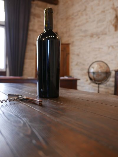 Wine Bottle And Corkscrew On Table