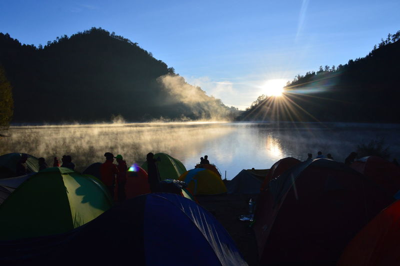 Group of people camping by lake in forest during sunset