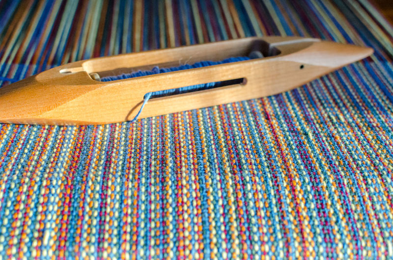 Close-up of wooden equipment on colorful thread