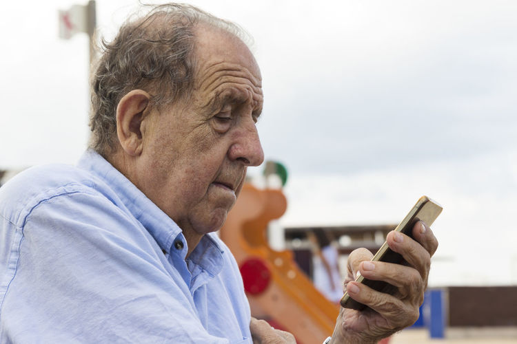 Elderly with his phone Adult Close-up Communication Connection Focus On Foreground Headshot Holding Males  Mature Men Men Mobile Phone One Person Outdoors Portrait Profile View Real People Senior Adult Senior Men Side View Surfing The Net Technology Using Phone Wireless Technology