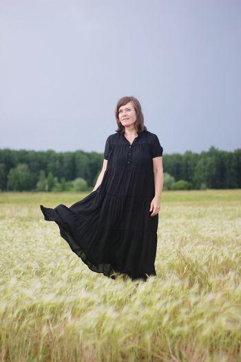 Woman in dress standing on field