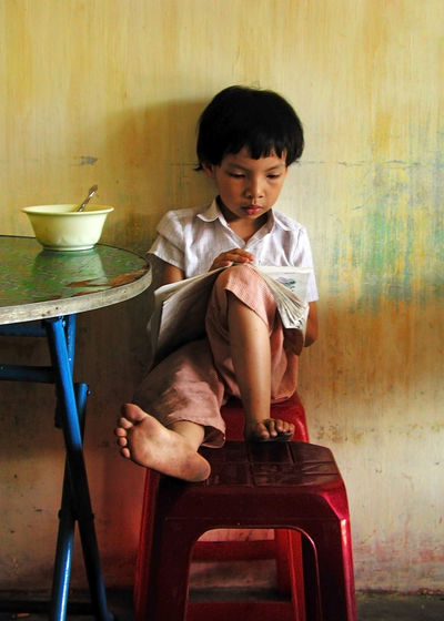 Young girl reading in noodle house in Hoi An, Vietnam Hoi An Reading Vietnam Youth Casual Clothing Chair Child Childhood Front View Full Length Girl Hairstyle Home Interior Indoors  Innocence Lifestyles One Person Real People Seat Sitting