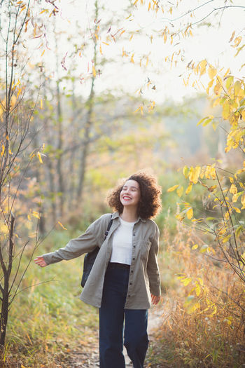 Portrait of smiling young woman standing on land during autumn