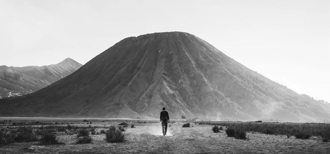 Rear view of man walking towards volcano