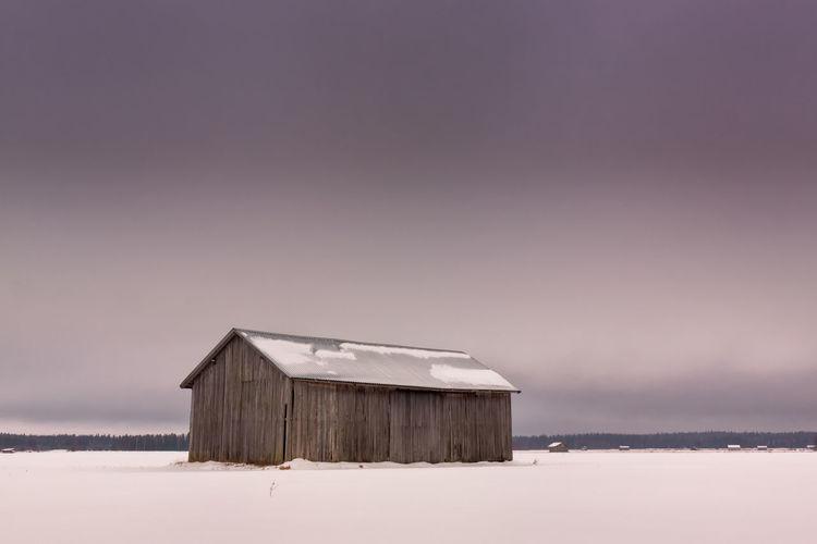 Barn on snowy landscape against sky