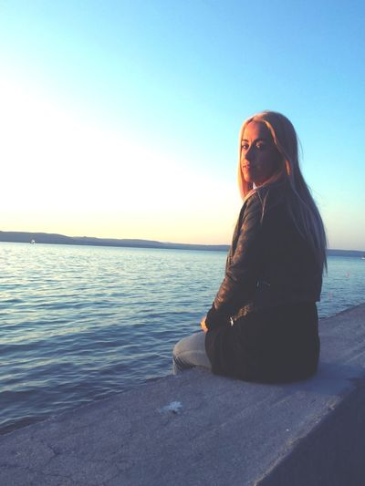 Portrait of young woman sitting on retaining wall by sea against clear sky during sunset