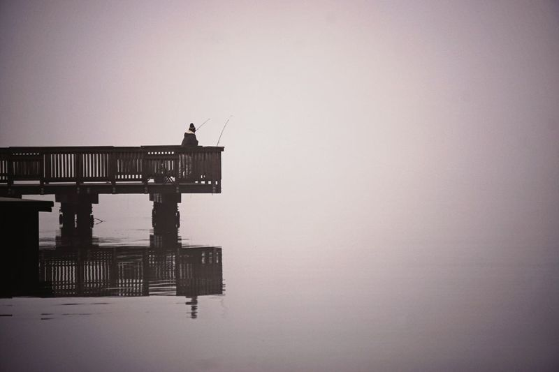 Rear view of person on pier fishing by lake during foggy weather