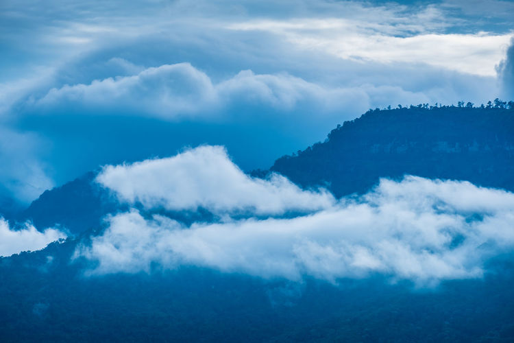 Low angle view of mountains seen through cloud against sky