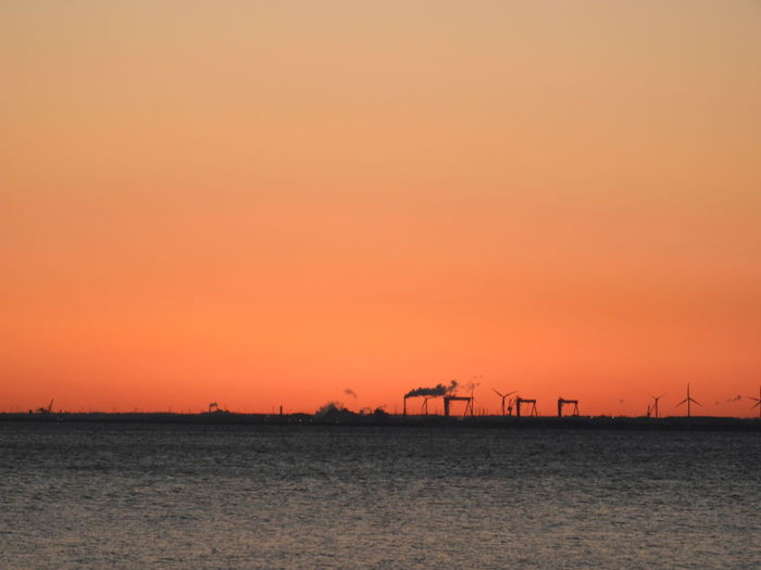 Alternative Energy Beauty In Nature Day Dusk Fuel And Power Generation Industry Nature No People Orange Color Outdoors Scenics Sea Silhouette Sky Sun Sunset Tranquil Scene Tranquility Water Waterfront Wind Power Wind Turbine Windmill
