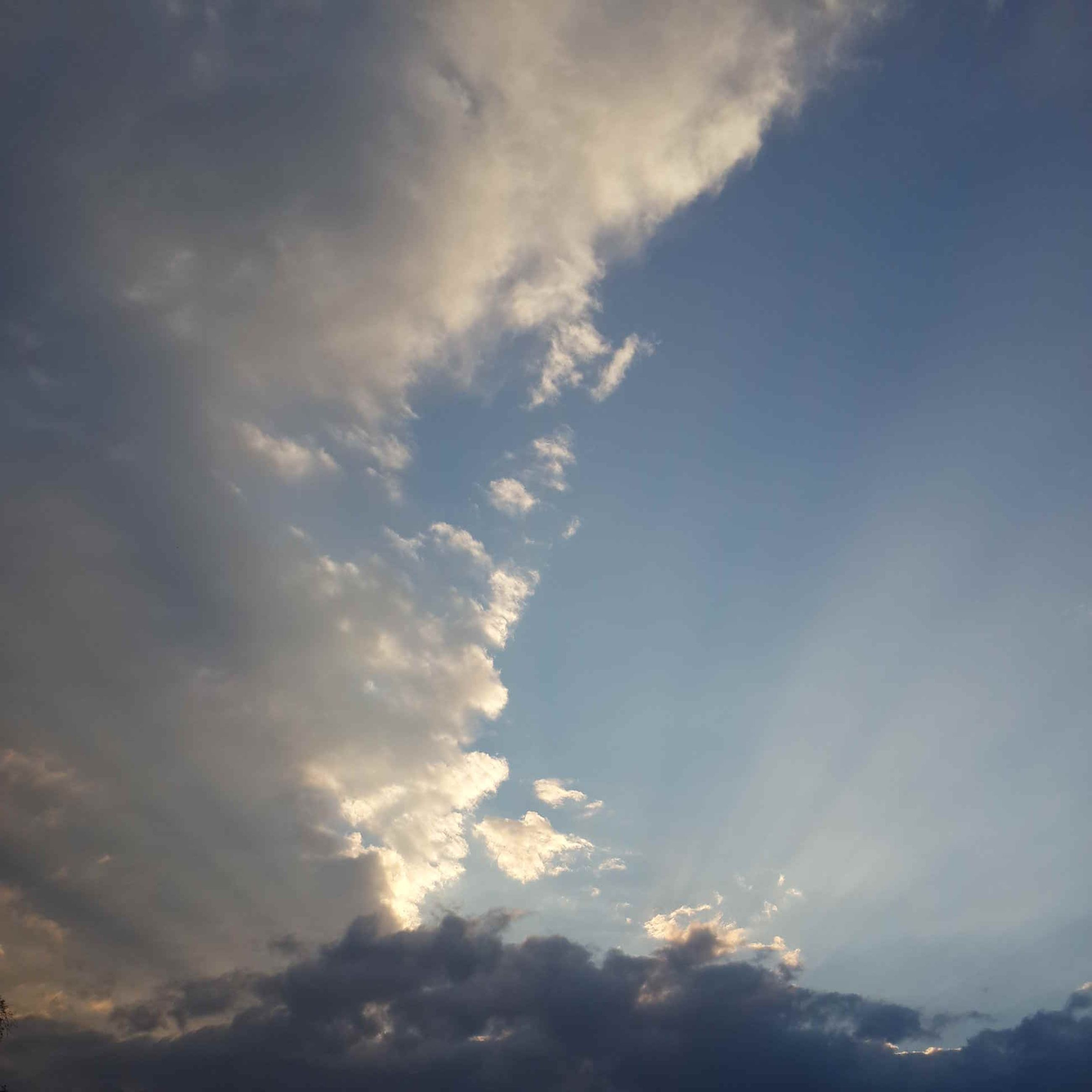 sky, low angle view, cloud - sky, beauty in nature, scenics, tranquility, sky only, nature, tranquil scene, cloudy, sunset, cloud, idyllic, cloudscape, sun, sunlight, sunbeam, backgrounds, outdoors, no people
