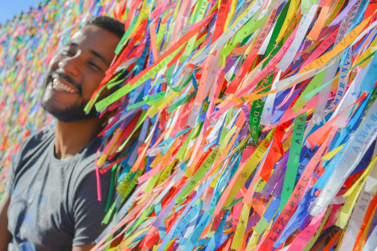 Smiling young man by colorful prayer ribbons