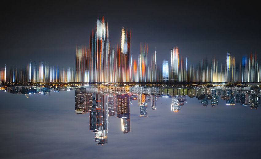 Illuminated commercial dock by river against sky at night