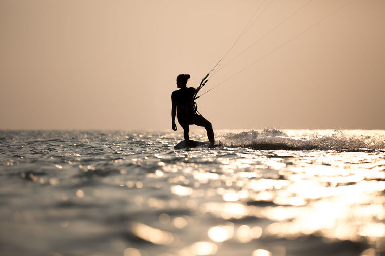 Silhouette man wakeboarding in sea against sky during sunset