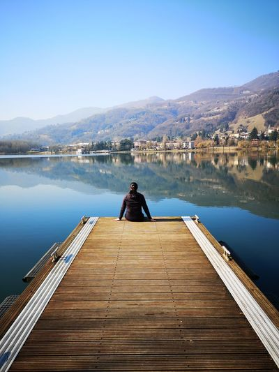 Girl looks at the lake of Endine, Bergamo Quiet Moment Nature Travel Destinations Lake Lake View Tranquillity Scene Tranquillity Girl Water Mountain Lake Sitting Clear Sky Jetty Adventure Pier Relaxation Wood - Material