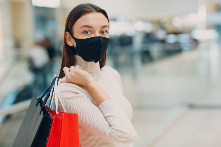 Portrait of woman wearing mask holding shopping bags outdoors