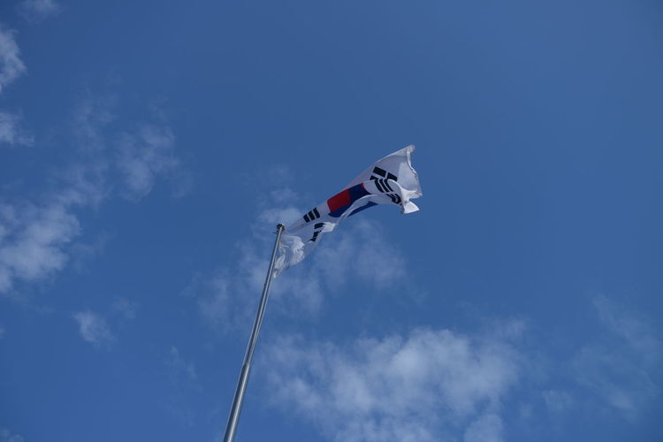 Low Angle View Sky Cloud - Sky Patriotism Flying Flag Nature Day Blue Wind No People Mid-air Environment Mode Of Transportation Pole Outdoors White Color Motion Freedom Independence National Icon Plane Korean Flag