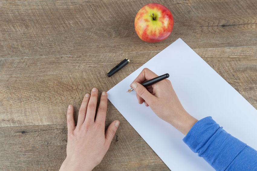 Woman hands holding fountain pen and blank piece of paper on wooden table with red apple Apple Copy Space Blank Paper Close-up Day Directly Above Education High Angle View Holding Human Body Part Human Hand Indoors  Learning Lifestyles One Person People Real People Table Top View Women Wood - Material Working