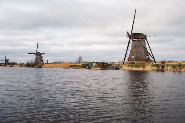 Traditional windmill by water against sky