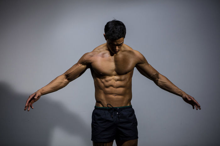 A male fitness model displaying his chiseled physique. Adult Asian  Human Body Man Shirtless Vietnamese Abs Arms Spread Chiseled Fitness Fitness Model Fitness Training Grey Wall Head Down Looking Away From Camera Male Medium Shot Model Muscles Muscular Build Pectoral Physique  Powerful Shorts Strong