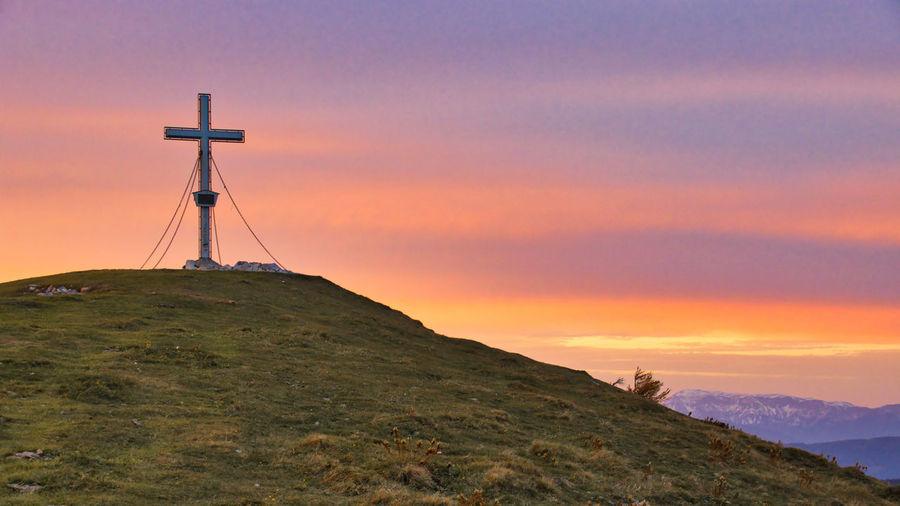 Cross on land against sky during sunset