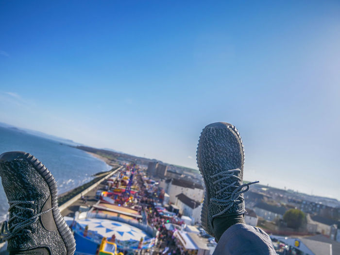 Architecture Blue Body Part Clear Sky Copy Space Day Human Body Part Human Foot Human Leg Jeans Leisure Activity Lifestyles Low Section Nature One Person Outdoors Real People Shoe Sky Unrecognizable Person Warm Clothing Winter