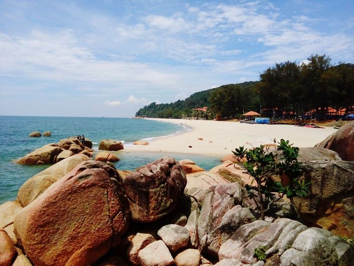 Scenic view of teluk cempedak with rocky shore against sky