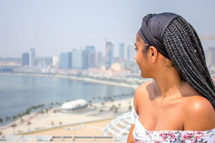 Young woman looking at beach and cityscape against sky