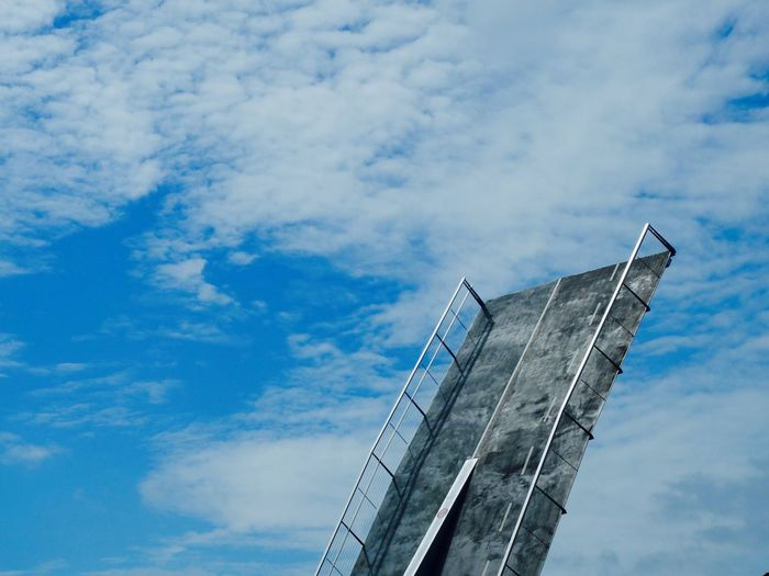 Low angle view of bascule bridge against cloudy sky