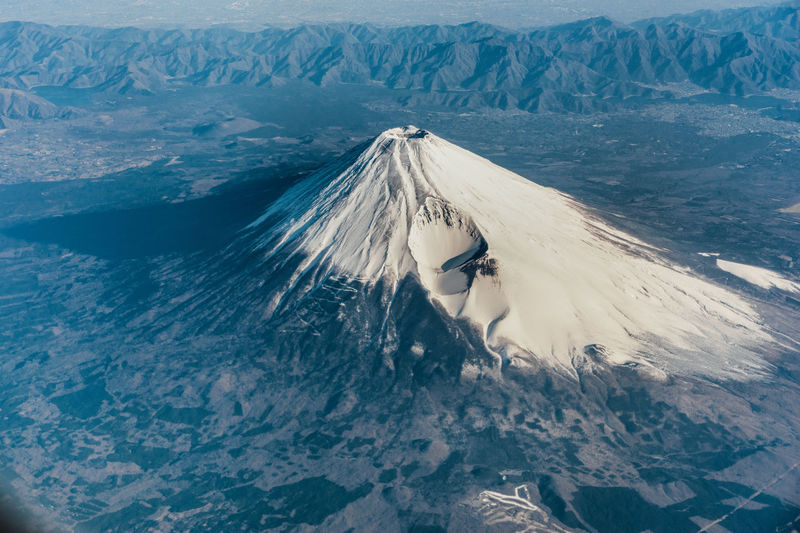 High angle view of woman on snowcapped mountain fuji by sea