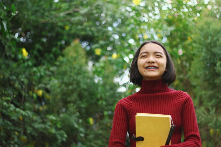 Close-up of girl holding book outdoors