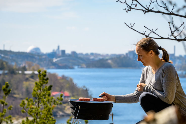 Side View Of Woman Preparing Meat On Barbecue By River