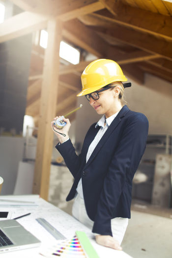 Architect wearing hardhat while working at construction site