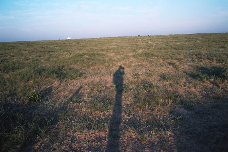 Shadow of person on field against sky