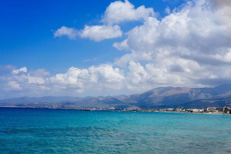 Scenic shot of calm sea against mountain range