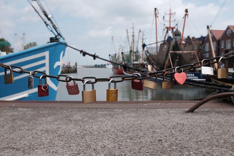 Love locks hanging on chain at harbor