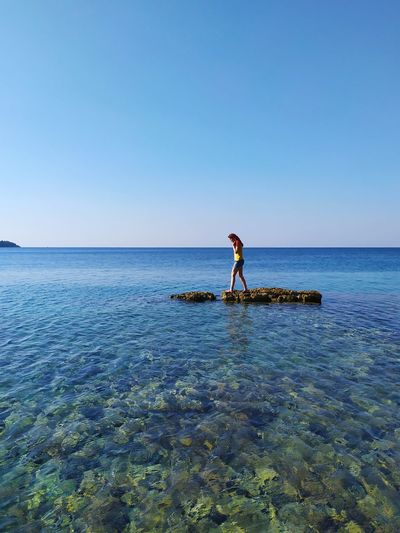 Man standing in sea against clear blue sky