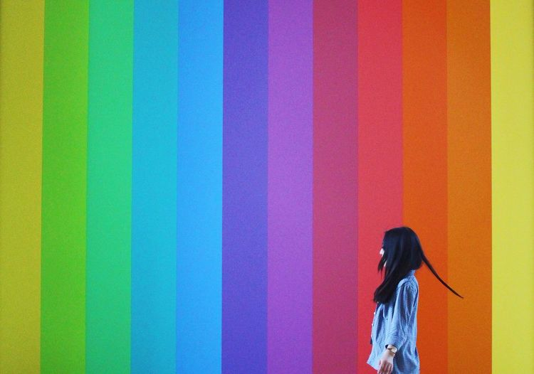 Side View Of Woman Standing By Colorful Wall